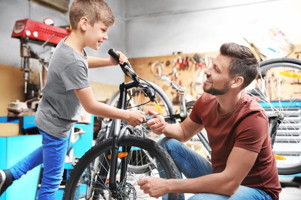 Dad and kid working on bike in garage